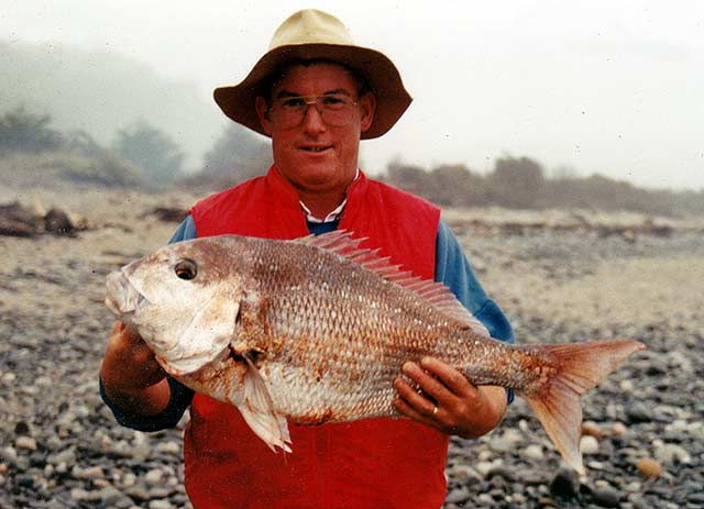 man at annie beach with a mokihinui snapper in hand
